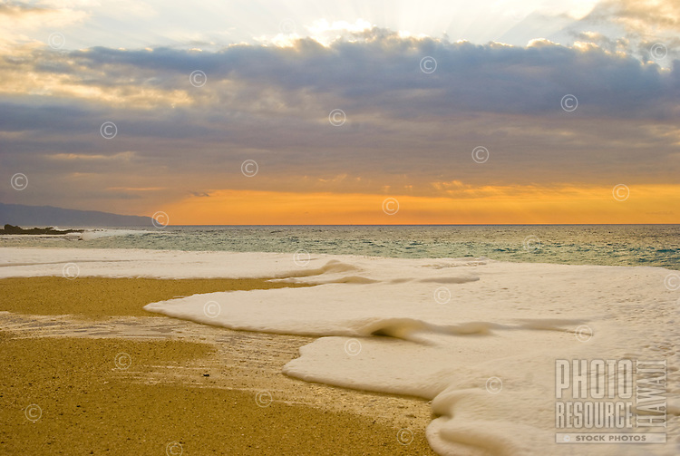Water sweeps the beach during a sunset at Ke Iki beach, on the North Shore of Oahu. Kaena Point can be seen in the background.