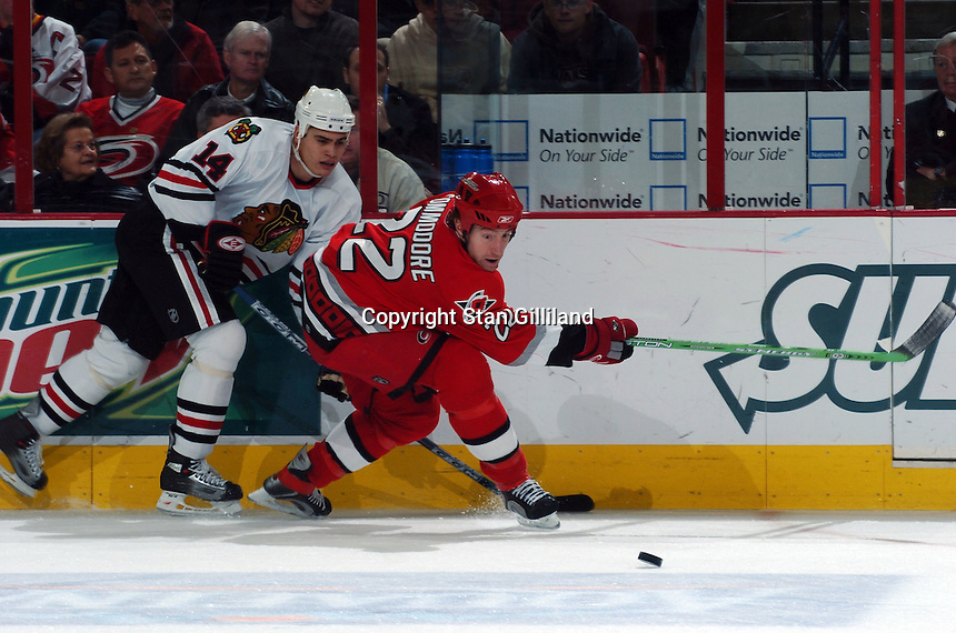 Carolina Hurricanes' Mike Commodore (22) tries to get rid of the puck while defended by the Chicago Blackhawks' Rene Bourque (14) Tuesday, Dec. 13, 2005 in Raleigh, NC. Carolina won 5-3.
