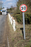 Thirty miles per hour road sign and lorry approaching