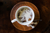 Coffee with swirls of cream served in a turned wooden saucer on a George Nakashima table at the George Nakashima gallery in Takamatsu, Japna.