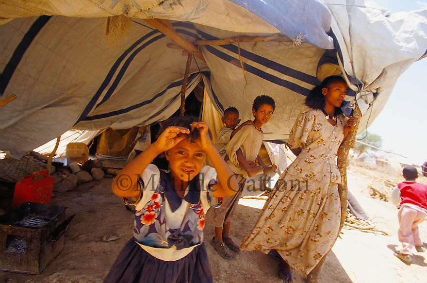 Eritrea - Debub- Family standing in their tent in an IDP camp. As a result of 30 years of war for independence against Ethiopia (from 1961 to 1991) and another 3 years from 1997 to 2000, there are 50,000 Eritreans currently living in internally displaced (IDP) camps throughout the country. These IDPs have fled three times in the last 10 years, each time because of renewed military conflict. They lived in relatives' homes when lucky enough, but mostly, the fled to the mountains, where they attempted to do what Eritreans do best, survive. Currently there is no Ethiopian occupation in Eritrea, but landmines prevent the IDPs from finally going home. .It is estimated that every Eritrean family lost two or three members to the war which makes the reality of the current emergency situation even more painful for Eritreans worldwide. Currently, the male population has been decreased dramatically, affecting the most fundamental socio-economic systems in the country. Among the refugee population, an overwhelming majority of families are female-headed, severely affecting agricultural production. For, IDPs in particular, 80% of households are female-headed..The unresolved border dispute with Ethiopia remains the most important drawback to Eritrea's socio-economic development, as national resources (human and material) continue to be prioritized for national defense. Eritrea is vulnerable to recurrent droughts and variable weather conditions with potentially negative effects on the 80 percent of the population that depend on agriculture and pastoralism as main sources of livelihood. The situation has been exacerbated by the unresolved border dispute, resulting in economic stagnation, lack of food security and increased susceptibility of the population to various ailments including communicable diseases and malnutrition..