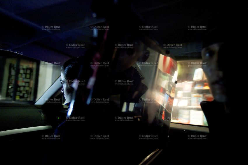 Switzerland. Geneva. A convict man seats in a police car on duty during the night. The inmate is a drug user, who got arrested after trying to enter a shop illegaly and steal articles. The man is a junkie who lives permanently in Geneva and is already well-known by the police for various burglaries and drug affairs. 29.03.12 © 2012 Didier Ruef.