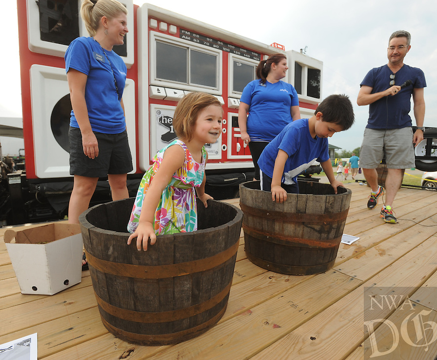NWA Democrat-Gazette/ANDY SHUPE<br /> Chloe Aldridge, 3, and brother, Daniel Aldridge (4, of Fayetteville stomp grapes Tuesday, Aug. 4, 2015, during the 117th annual Tontitown Grape Festival. The festival continues through Saturday. Visit nwadg.com/photos to see more photographs from the festival.