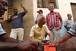 Men play dominoes on the street in Havana while one complains after losing the previous game.