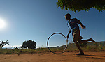 A boy runs as he rolls a bicycle wheel along a path in Kaluhoro, Malawi. With support from the Ekwendeni Hospital AIDS Program, members of his family and other families in the village are participating in a Building Sustainable Livelihoods program, working together to earn and save money, raise more nutritious food, and receive vocational training.