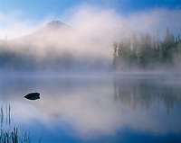 ORCAC_114 - USA, Oregon, Willamette National Forest, North (left) and Middle Sister (right) reflect in Scott Lake while early morning fog swirls above the lake.