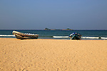 Boats on tropical beach at Nilavelli, Trincomalee, Sri Lanka, Asia with Pigeon Island in background