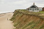 A person on the sandy beach inspecting the coastal cliff erosion near Happisburgh on the Norfolk Coast, United Kingdom.