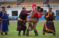 Ulaanbaatar, Mongolia, July 2003..Competitors in the Mongolian Wrestling championships in the national Naadam at Ulaanbaatar central stadium. Mongolian wrestling champion Usukhbayar finally succeeds in throwing his opponent, ending a marathon 3 hour semi-final match. Usukhbayar went on to wion the final, becoming champion for the second time.