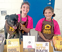 Photo submitted<br /> Sisters McKenna Baum, left, and Jaelyn Baum sold dog treats at the Tailwaggers Pool Pawty, which took place at the Siloam Springs Aquatic Center in September. Their business, Bark Bites, donates 20 percent of its proceeds to Tailwaggers. The girls were inspired by their dog Charlie, left, who was adopted from the Siloam Springs Animal Shelter in 2016, and their love for animals.