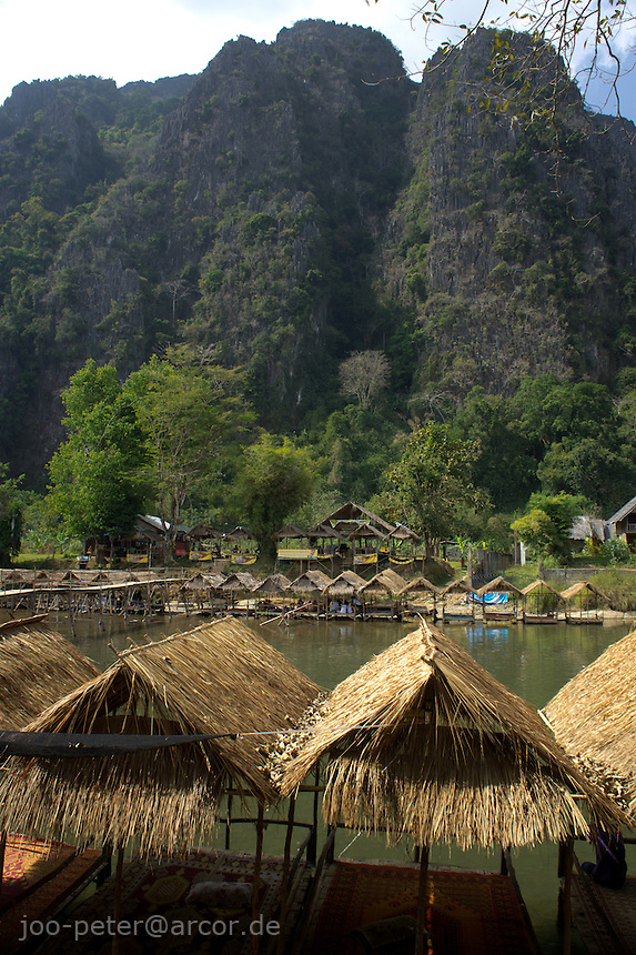 old backpacker-style traditional  bamboo and palm-leaf guest houses in Vang Vieng at the river with mountains in the background, Laos, 2012