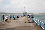 People fishing from harbour breakwater pier at Weymouth, Dorset, England, UK