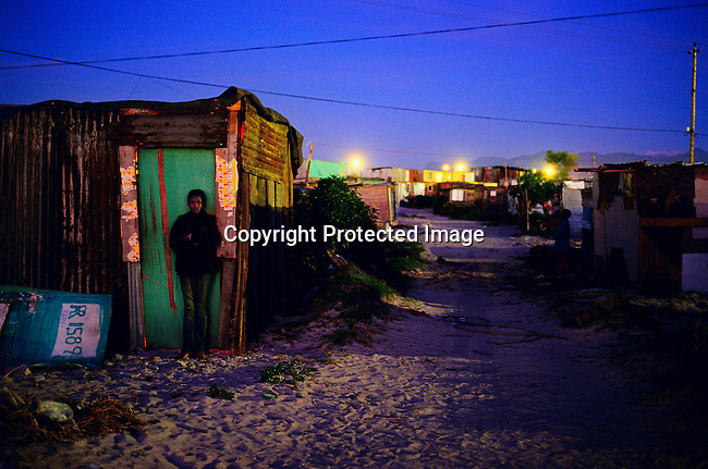 A teenage girl stands outside the family home at night in Khayelitsha, outside Cape Town, South Africa. About 1 million people live here in poor conditions, most of them coming from the rural areas to look for work in Cape Town. (Photo by: Per-Anders Pettersson)