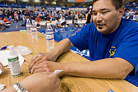 "Travis Cole from Hughs, Alaska, gets his knuckles tended to following the knuckle hop or seal hop competition at the 2008 World Eskimo Indian Olympics, Fairbanks, Alaska. A game of endurance, pain and strength. The object is to see how far one can go in a ""push-up"" hopping position, with elbows bent and knuckles down."