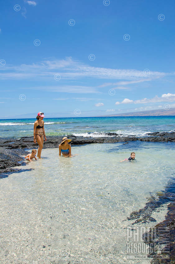Two local mothers and their children play in the tide pools at a beach in Puako, Big Island.