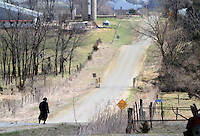An Amish woman walks a gravel road south of Drakesville in southeast Iowa's Davis County.   It is among only a handful of rural Iowa counties in the 2010 Census to gain population (2.4 percent).  Much of that population growth is due to a steadily growing Amish population.  (Christopher Gannon/The Des Moines Register)