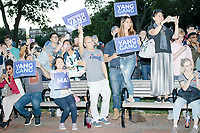 """People cheer as entrepreneur and Democratic presidential candidate Andrew Yang arrives to speak to a large crowd in Cambridge Common near Harvard Square in Cambridge, Massachusetts, on Mon., September 16, 2019. Yang's unlikely presidential bid is centered on his idea for a """"Freedom dividend,"""" which would give USD$1000 per month to every adult in the United States. After appearing in three Democratic party debates, Yang has risen in polls from longshot candidate to within the top 10.   In the picture, people can be seen holding MATH signs or wearing hats that say MATH. The slogan MATH is now said to mean """"Make America Think Harder"""" and the candidate frequently sites statistics and mathematics in his speeches."""