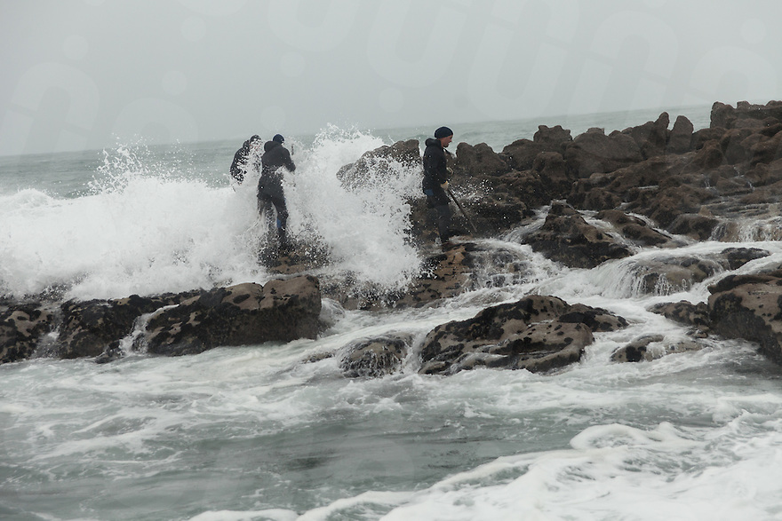 December 13, 2011 - Laxe (La Coruña). A group of percebeiros gets his by a wave. Not even the gale force eight and heavy rains can stop them, Christmas' time is too important. © Thomas Cristofoletti 2011