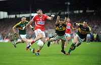 18-07-2015: Cork's Paul Kerrigan blasts the ball pass Kerry palyers Jonathon Lyne and David Moran to score a goal in the Munster senior football championship final replay at Fitzgerald Stadium, Killarney, on Saturday night. <br /> Photo: Don MacMonagle - macmonagle.com