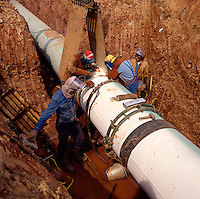 .Welders working on joint in large long-distance gas/oil pipeline. Scotland.