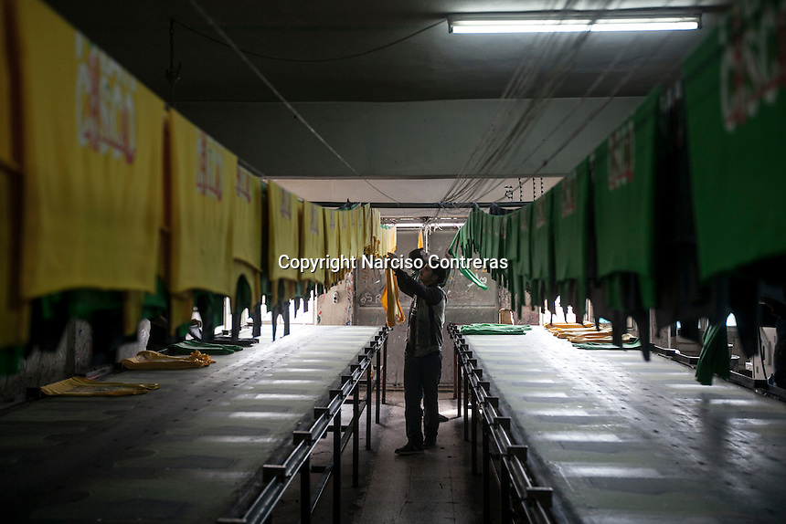 February 13, 2016: Syrian refugees work in the printing process of t-shirts in a print factory in Gaziantep. The factory is owned by Sherif Khalil (not pictured), a Syrian Kurdish businessman that fled into Turkey during the war in the neighbouring country and currently owns the factory that also gives job to other refugees from Syria.