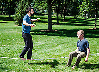 Owner of Rocky Mountain Slackline Dakota Collins (right), works with The Adventurist columnist, Clint Carter at Spring Park in Ft. Collins, Colorado, Sunday, August 27, 2017. Carter take on a vertigo-inducing highline that stretches across a traverse after only 4 days of training.<br /> <br /> Photo by Matt Nager