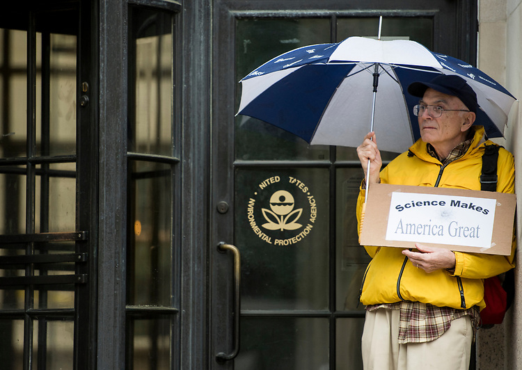 UNITED STATES - APRIL 22: A protester seeks shelter from the rain in front of the Environmental Protection Agency during the March for Science in Washington on Earth Day, Saturday, April 22, 2017. Thousands of pro-science and environmental activists rallied on the National Mall before marching towards the Capitol. (Photo By Bill Clark/CQ Roll Call)