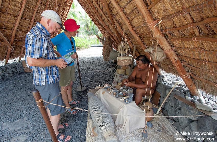 Tourists watching native Hawaiian man make Hawaiian artifacts in Pu'uhonua o Honaunau place of refuge national historical park, Big Island, Hawaii