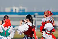 Young Czech girls and boys, wearing folk costume, take pictures during the arrival of the Pope Benedict XVI at the Prague Airport, Czech Republic, 26 September 2009.