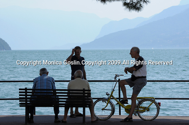 Four men are talking, two men are sitting on a bench and one is on a yellow bike, while they admire the view in Domaso, a town on Lake Como, Italy.
