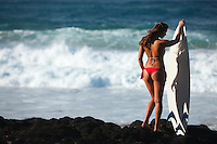 Beautiful young surfer modeling with surfboard on volcanic rocks in Hawaii.