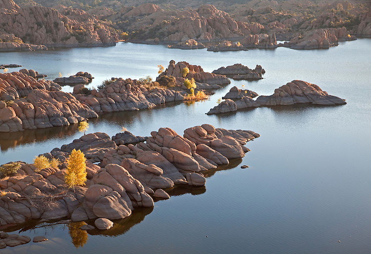 Granite rocks and golden cottonwoods (Populus fremontii)during autumn at Watson Lake, Arizona, USA