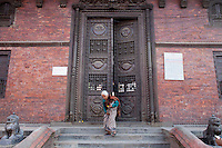 An old woman exits a temple after prayer in Kathmandu, Nepal