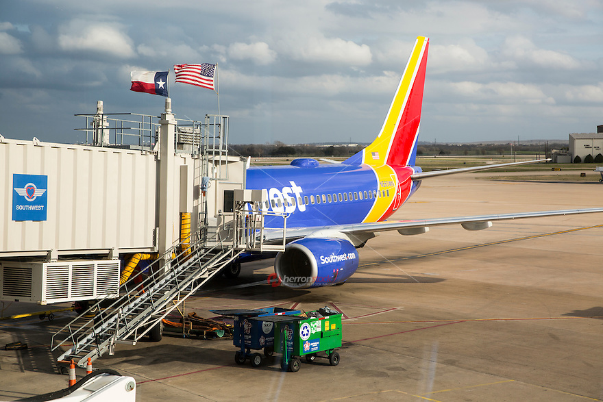 View looking out of the terminal window of an jet airplane parked at the airport gate with the Texas and USA flags flying in the breeze at Austin–Bergstrom International Airport - Stock Image.