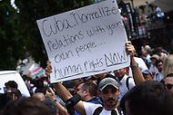 Washington, DC - July 20, 2015: A man holds a sign across from the Cuban Embassy as Cuban officials raise the flag at the re-opened embassy July 20, 2015. The embassy reopened after the United States began normalizing diplomatic relations with Cuba. (Photo by Don Baxter/Media Images International)