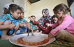 Zahra Al Hussein feeds her children inside her tent  in a settlement of Syrian refugees in Minyara, a village in the Akkar district of northern Lebanon. Lebanon hosts some 1.5 million refugees from Syria, yet allows no large camps to be established. So refugees have moved into poor neighborhoods or established small informal settlements in border areas. International Orthodox Christian Charities, a member of the ACT Alliance, provides a variety of support for families in this settlement, including some meals prepared in a community kitchen. Al Hussein is originally from the Syrian city of Homs.