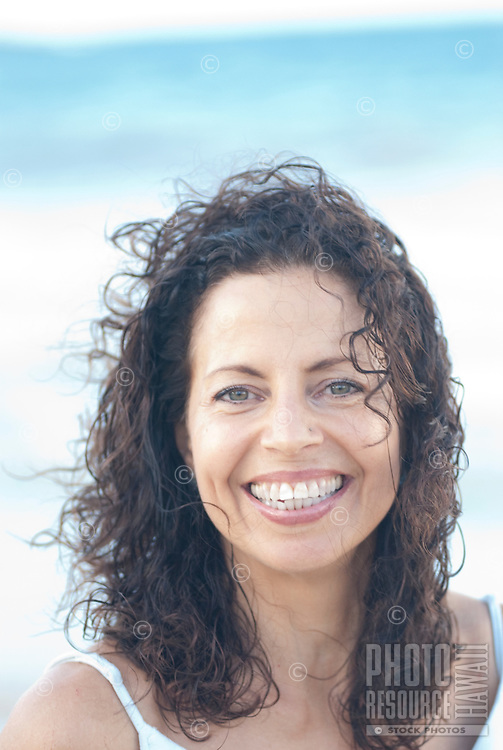 Big smile on a beautiful curly haired woman at age 50 taken at Kailua beach