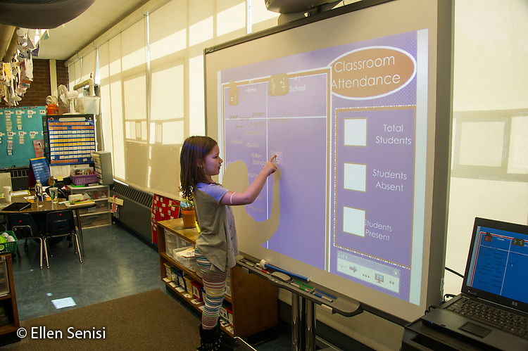 MR / Schenectady, NY. Zoller Elementary School (urban public school). Kindergarten inclusion classroom. Student (girl, 5) signs herself in for the day on digital whiteboard set up with attendance taking software. MR: Cas12. ID: AM-gKw. © Ellen B. Senisi.