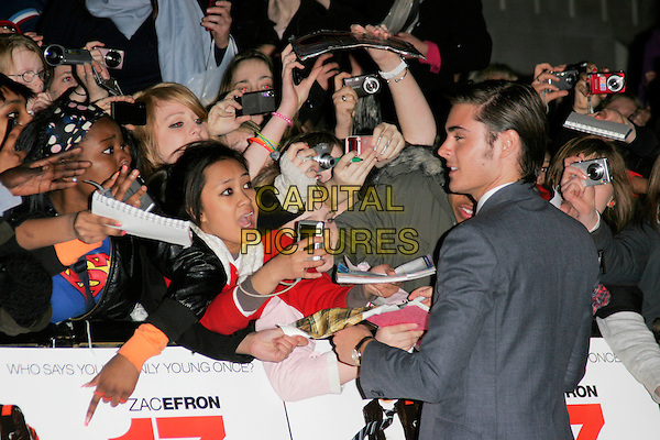 "ZAC EFRON.""17 Again"" UK film premiere at the Odeon West End cinema, London, England..March 26th, 2009.arrivals half length grey gray suit jacket profile back behind rear fans crowd audience signing autographs .CAP/AH.©Adam Houghton/Capital Pictures."