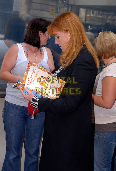 SARAH FERGUSON, DUCHESS OF YORK.Seen leaving BBC Radio 2 building, London, England, UK, .14th August 2009..royal Fergie half length black coat Signing copy of her book Little Red To The Rescue autograph side profile .CAP/IA.©Ian Allis/Capital Pictures