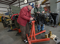 NWA Democrat-Gazette/ANDY SHUPE<br /> Tom Schuessler (left) of Rogers and JD Smith of Bella Vista lift an engine assembly Tuesday, Nov. 27, 2018, and attach it to an engine stand while working on a Vietnam War-era 1962 M151 Military Utility Tactical Truck at the Arkansas Air and Military Museum. The vehicle was leaking oil from a rear main bearing seal, so the two were making the repair.