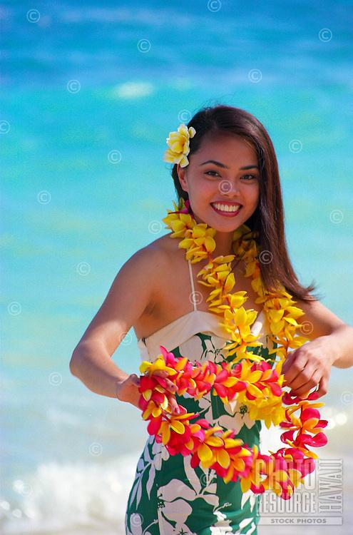 Beautiful polynesian girl with plumeria leis on the beach
