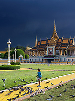 A young girl feeding pigeons and a Storm approaching over the Grand Performance Hall at the Grand Palace in Phnom Penh, Cambodia.