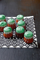Little cakes iced a fresh green stand on an ornate paper doily