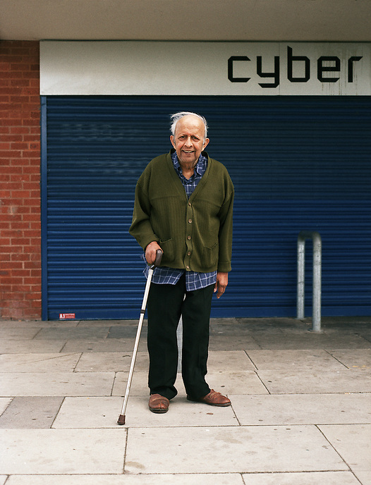 HATTERSLEY, UK - Carl, an elderly resident of a residential care home on the Hattersley Estate poses for a portrait in front of the recently closed-down Cyber Cafe in Hattersley's main shopping precinct.. .The Hattersley Estate was created in the early 1960s to house residents displaced by the slum clearances of inner city Salford and Manchester and soon gained notoreity between 1963 and 1965 as the home to the Moors Murderers, Myra Hindley and Ian Brady. Lying in a relatively isolated area on the edge of the Pennines, residents today continue to wait for the investment and infrastructure promised to them decades ago. In the gap between promise and reality, a unique characted formed during years of adversity continues to thrive on the estate.