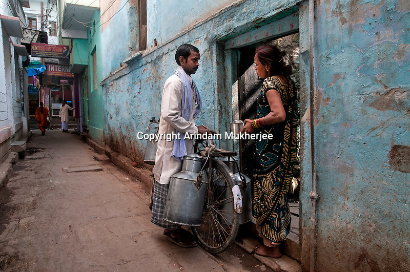 An Indian Milk man with his customer at a lane in Varanasi, Uttar Pradesh, India.