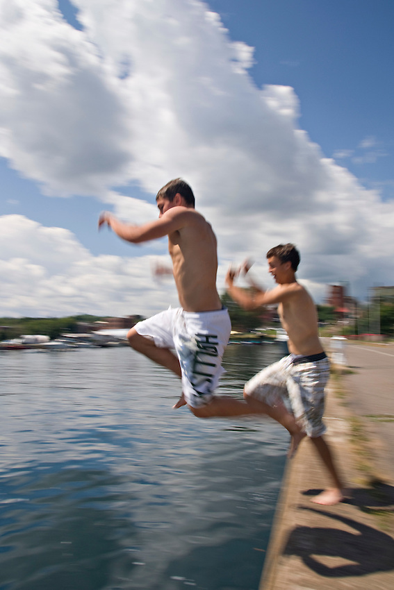 Kids jump off the sea wall into Lake Superior at Mattson Lower Harbor Park of Marquette Michigan on Lake Superior.