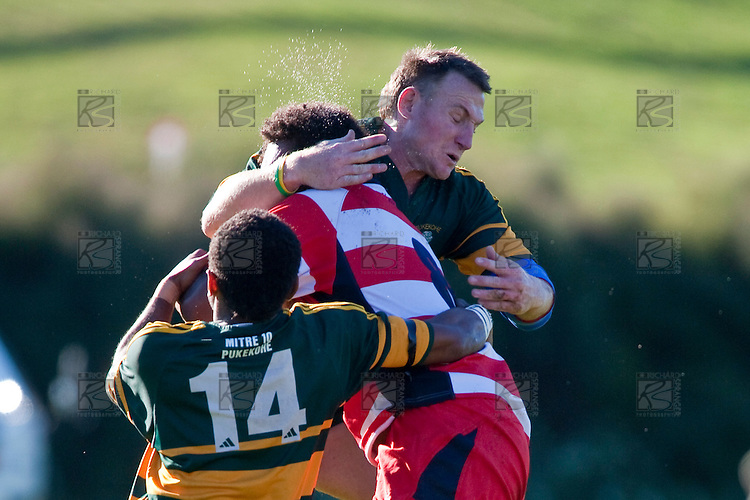 Viliame Setitaia gets hits in a sandwich tackle between Peni Buakuka & Nigel Watson. Counties Manukau Premier Club Rugby game between Pukekohe & Karaka played at Colin Lawrie Fields Pukekohe on Saturday May22nd 2010..Pukekohe won the game 32 -28 after trailling 3 - 22 at halftime.