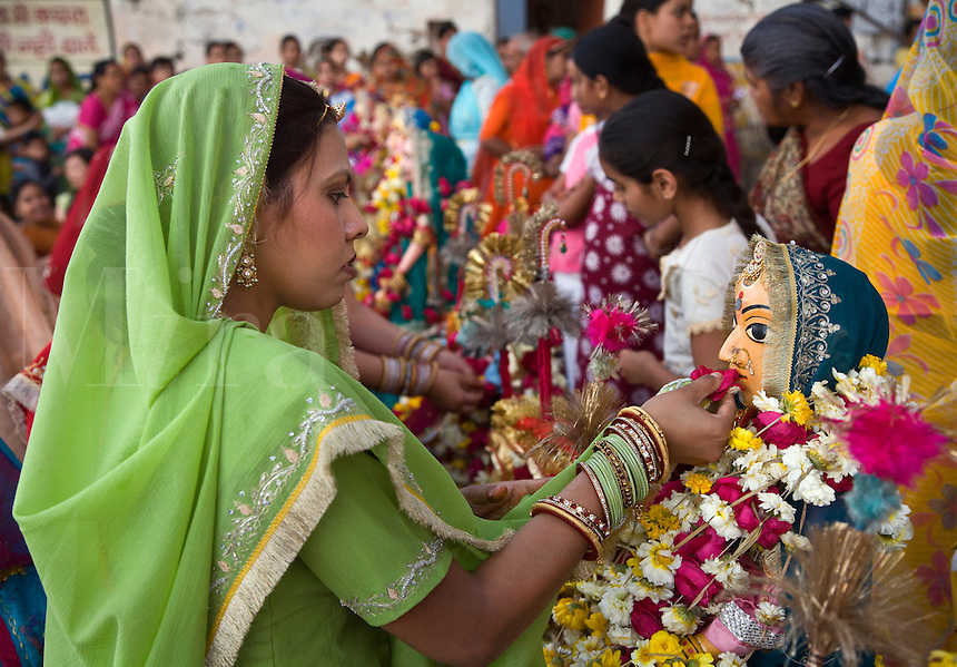 A Rajasthani woman makes a flower offerting to Shiva's wife PARVATI at the GANGUR FESTIVAL also known as the MEWAR FESTIVAL in UDAIPUR - RAJASTHAN, INDIA