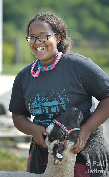 Sara Goitom, a resettled refugee from Eritrea, braces her sheep on a farm in Linville, Virginia, on July 18, 2017. Goitom and other refugee youth, resettled in the area by Church World Service, are preparing to show sheep and goats in a county fair.<br /> <br /> Photo by Paul Jeffrey for Church World Service.